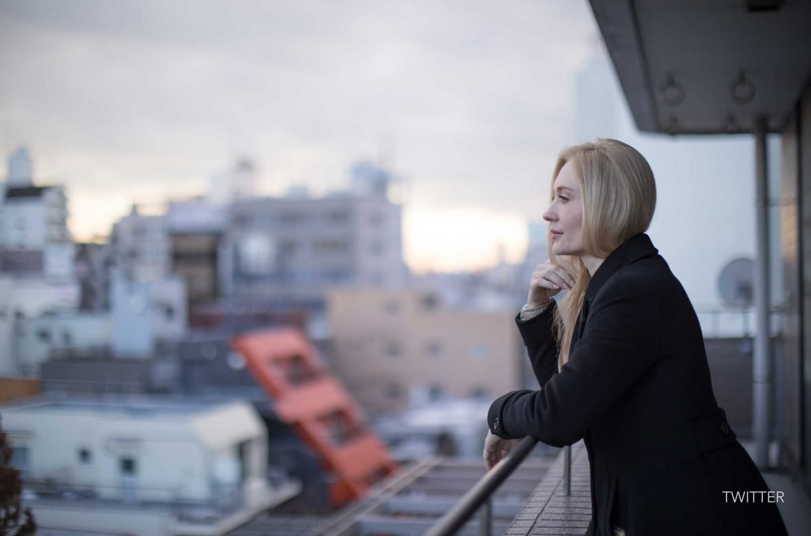 An employee takes a moment to ponder life, while looking out at the Tokyo cityscape.