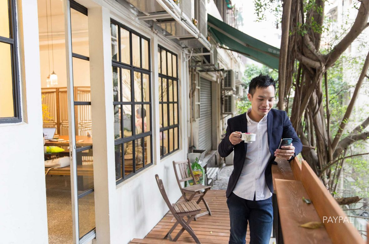 A young Hong Kong executive takes a coffee break and checks his phone.