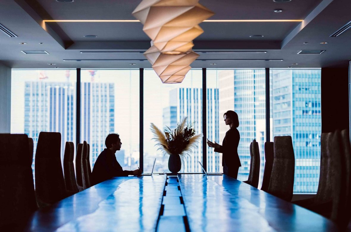 Two employees have a serious discussion in a high-rise office, with the Tokyo cityscape in the background.
