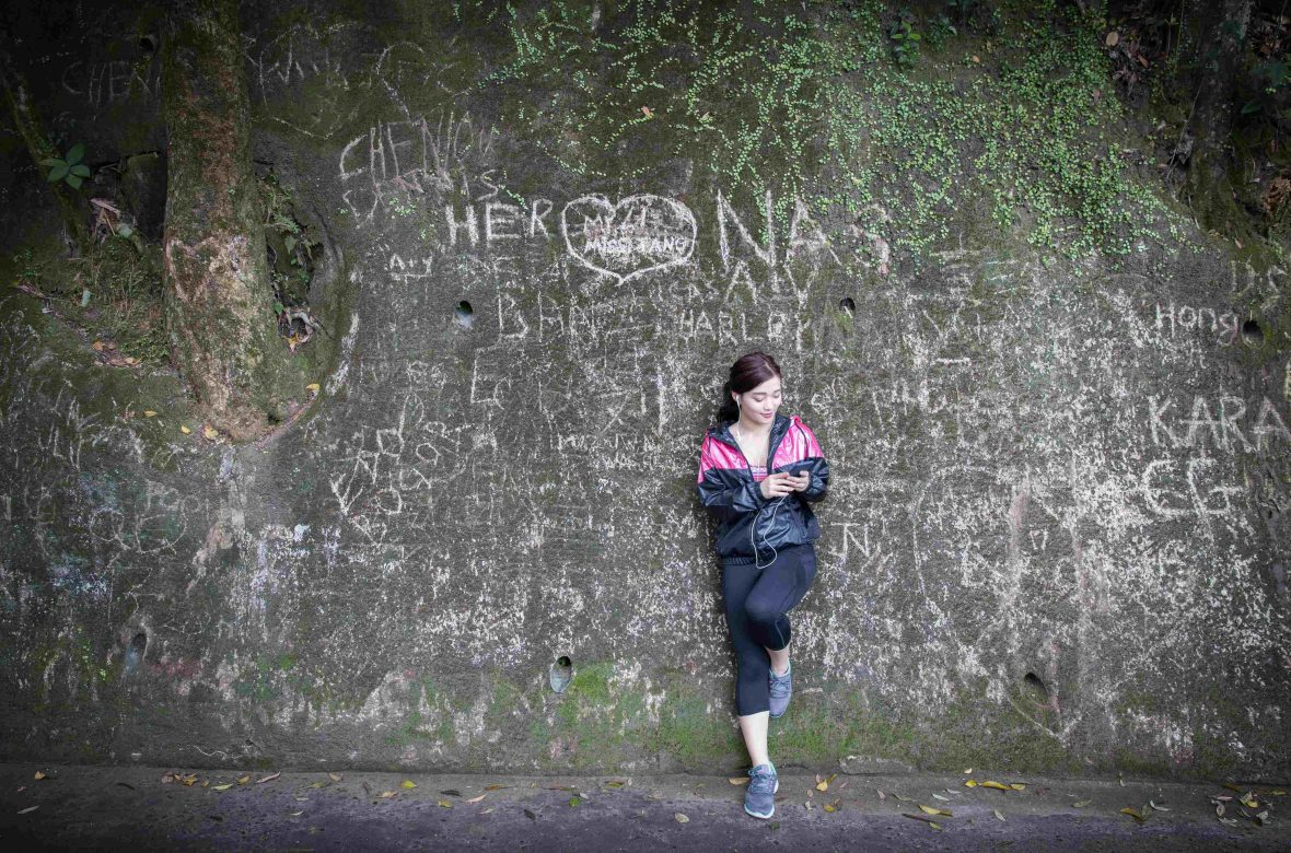A young Hong Kong executive stops and checks her cell-phone while hiking up to Victoria Peak.